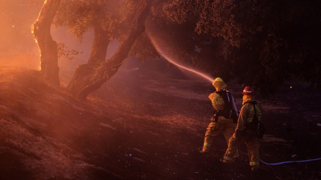 Firefighters spray water near a burning house in the Twin Pines Road area at the Silver Fire near Banning, California.