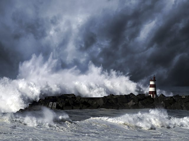 Storm waves over beacon of the harbor of Povoa do Varzim, Portugal - enhanced sky