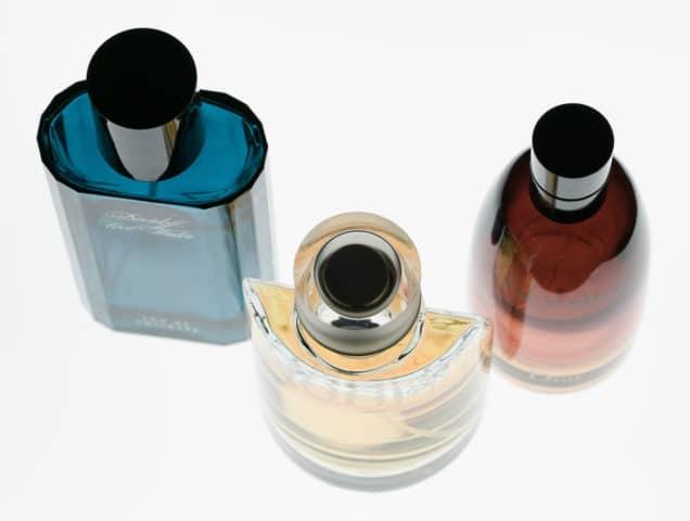 Drei Parfum-Flakons auf einer Leuchtplatte.